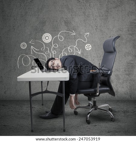 Portrait of male entrepreneur in business suit, sitting on chair while sleep on laptop at desk - stock photo