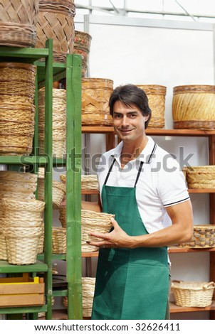 portrait of male florist arranging flowerpots on shelf in nursery - stock photo