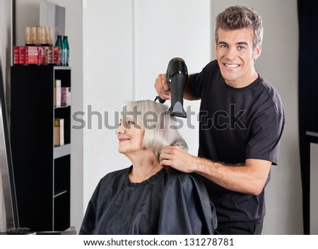 Portrait of male hairdresser with dryer setting up female customer's hair in parlor
