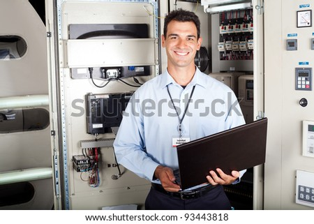 portrait of male industrial engineer in front of machinery - stock photo