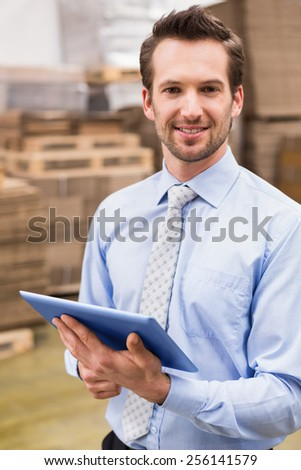 Portrait of male manager using digital tablet in warehouse - stock photo