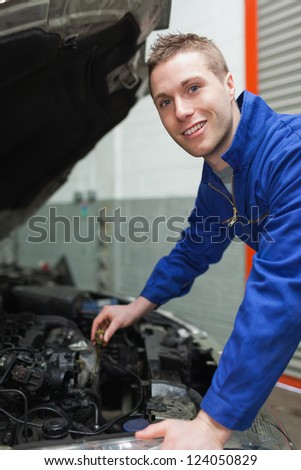 Portrait of male mechanic checking car engine oil