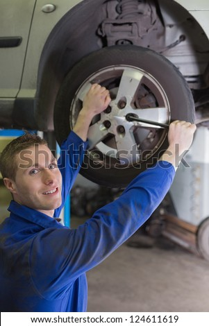 Portrait of male mechanic fixing car tire with wrench in garage - stock photo