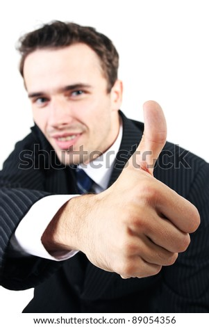 Portrait of male model, man, businessman in suit smiling and showing ok, allright with his thumb - focus on hand - face out of focus - made in studio on white background, isolated on white - stock photo