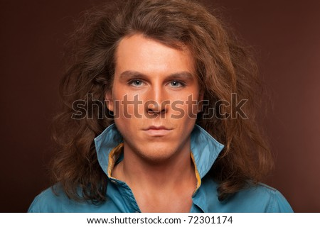 Portrait of male model with long hair and makeup on brown background - stock photo