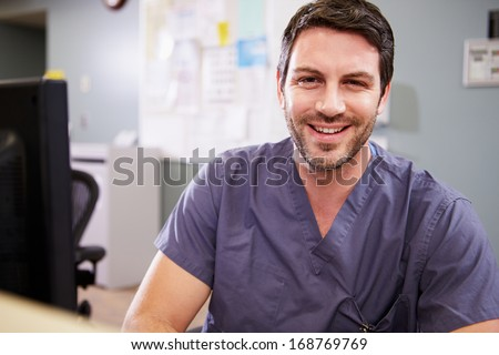 Portrait Of Male Nurse Working At Nurses Station - stock photo