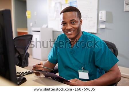 Portrait Of Male Nurse Working At Nurses Station - stock photo