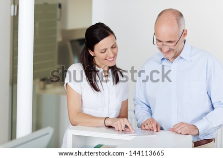 Portrait of male patient and receptionist looking at document at counter - stock photo
