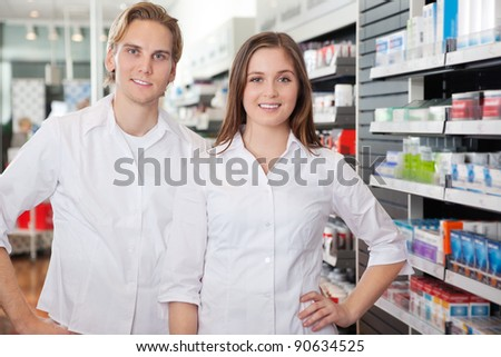 Portrait of male pharmacist technician standing with female colleague - stock photo