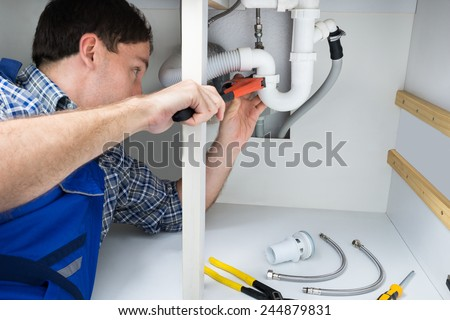 Portrait Of Male Plumber Fixing A Sink In Bathroom - stock photo