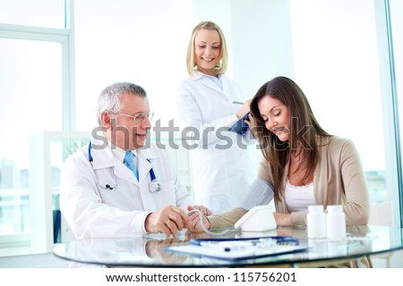 Portrait of male practitioner measuring blood pressure of patient with nurse near by - stock photo