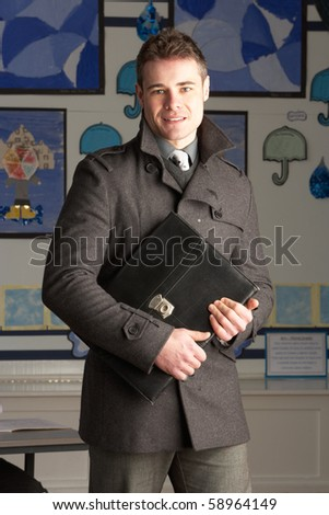 Portrait Of Male Primary School Teacher Standing In Classroom - stock photo