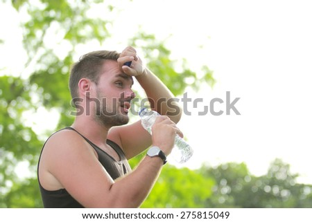portrait of male runner wiping his sweat while holding a bottle of water during break after tired running - stock photo