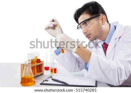 Portrait of male scientist makes chemical research by using chemical liquid, isolated on white background