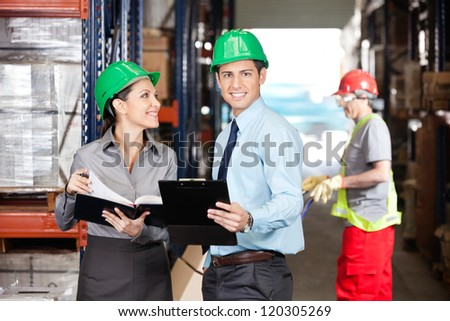 Portrait of male supervisor with colleague and foreman working at warehouse - stock photo