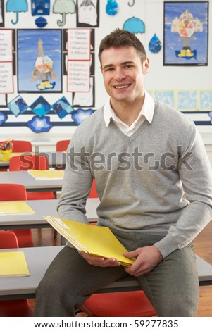Portrait Of Male Teacher Sitting At Desk In Classroom - stock photo