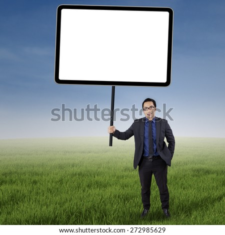 Portrait of male worker in business suit, standing on the meadow while holding an empty board - stock photo