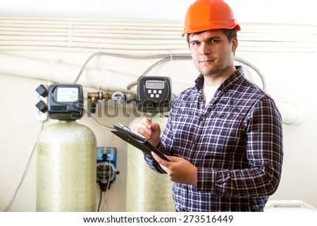 Portrait of male worker inspecting work of industrial equipment - stock photo