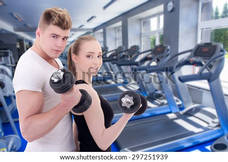portrait of man and woman in sportswear with dumbbells in modern gym - stock photo