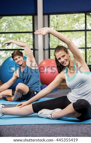 Portrait of man and woman performing fitness exercise at gym - stock photo
