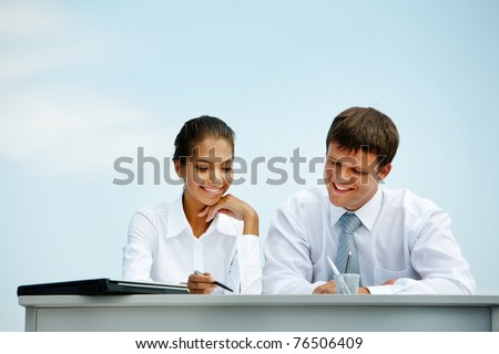 Portrait of man and woman sitting at the desk and interacting with each other - stock photo