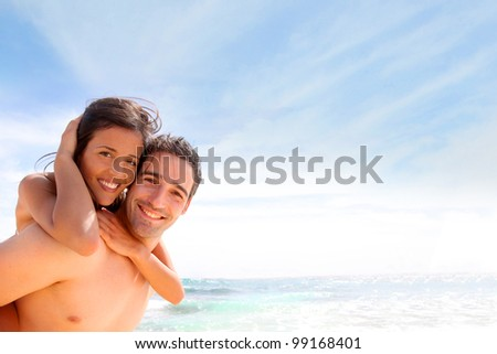 Portrait of man carrying girlfriend on his back - stock photo