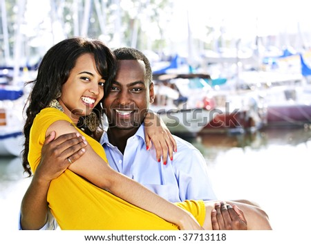 Portrait of man carrying his girlfriend standing at harbor - stock photo