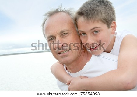 Portrait of man carrying young boy on his back - stock photo