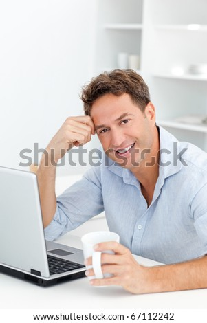 Portrait of man drinking coffee while working on his laptop in the kitchen - stock photo