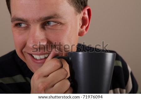 Portrait of man drinking hot beverage. Relatively short DoF. Sharp face, eyes. - stock photo