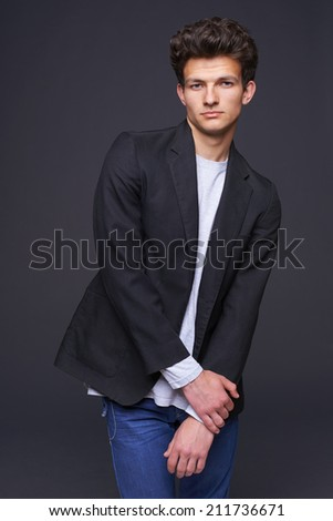 Portrait of man fashion model with modern haircut posing over dark background