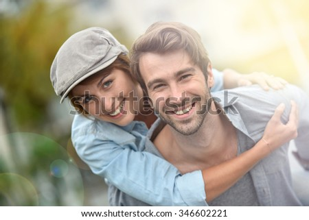 Portrait of man giving piggyback ride to girlfriend