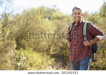 Portrait Of Man Hiking In Countryside Wearing Backpack - stock photo