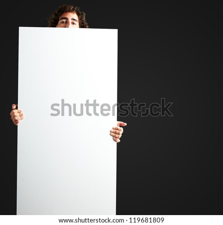 Portrait Of Man Holding a blank billboard against a black background