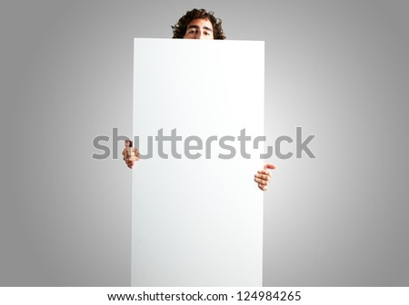 Portrait Of Man Holding a blank billboard against a grey background - stock photo