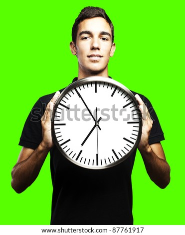 portrait of man holding clock against a removable chroma key background - stock photo