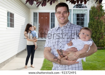 Portrait of man holding his daughter with wife standing behind holding son - stock photo