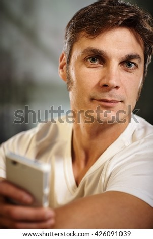 Portrait of man holding mobilephone, looking at camera. - stock photo
