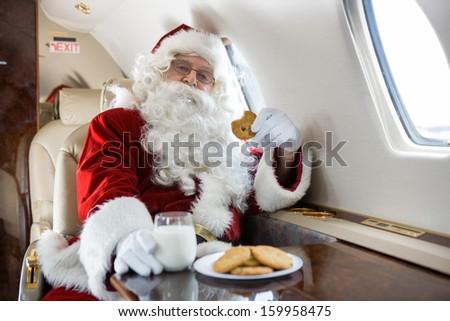 Portrait of man in Santa costume having cookies and milk in private jet - stock photo
