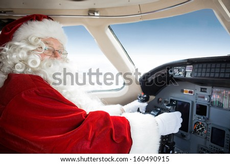 Portrait of man in Santa costume holding control wheel in cockpit of private jet - stock photo
