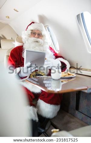 Portrait of man in Santa costume holding digital tablet in private jet - stock photo