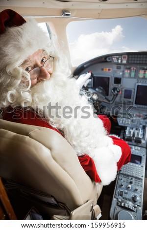 Portrait of man in Santa costume sitting in cockpit of private jet - stock photo