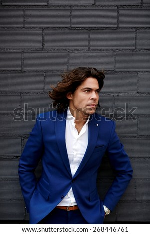 Portrait of man in suit posing outdoors looking worried and concentrated, fashionable confident businessman with hands in the pockets standing on beautiful black background for your text message - stock photo