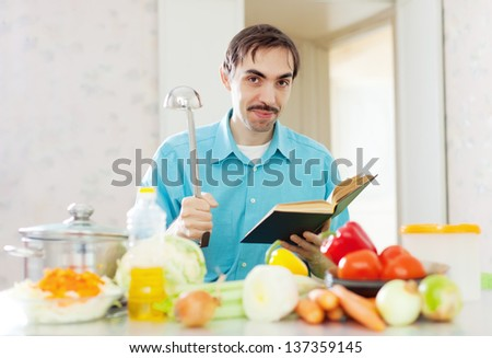 Portrait of man ladle pan and cookbook in domestic kitchen at home - stock photo