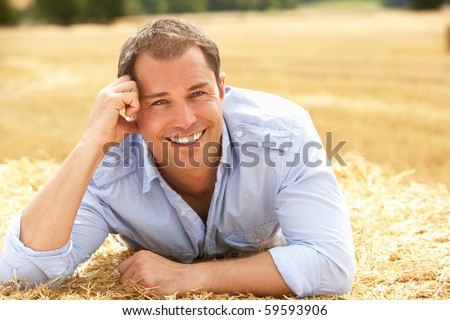Portrait Of Man Laying In Summer Harvested Field - stock photo