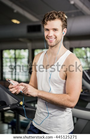 Portrait of man listening to music on treadmill at gym - stock photo