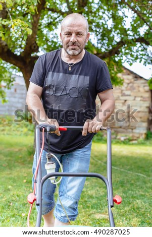 Portrait of man mowing lawn