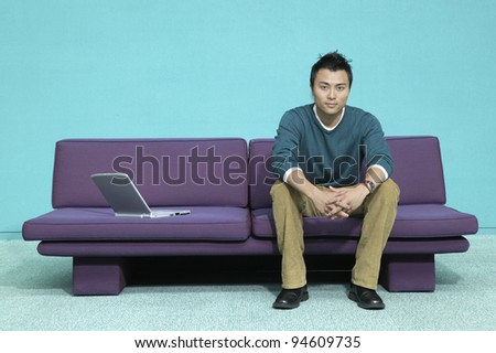 Portrait of man on couch with laptop - stock photo