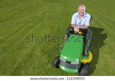 Portrait of man on riding lawn mower - stock photo
