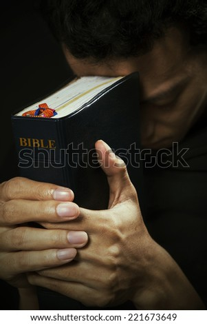 Portrait of man praying with bible - stock photo